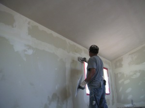 Filipe plastering the office wall